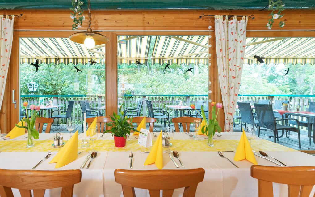 Blick von einem Tisch im Gastraum auf die Terasse im Naturfreunde Bootshaus St. Pölten